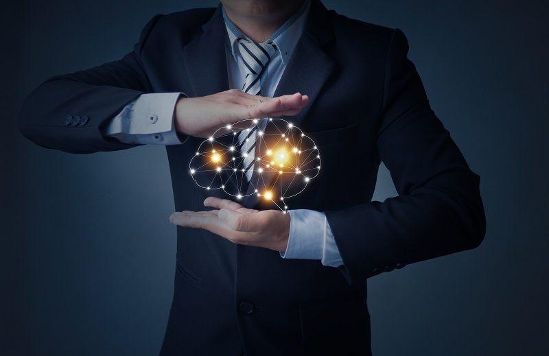 Eine Person hält ein virtuelles Gehirn zwischen seinen Händen