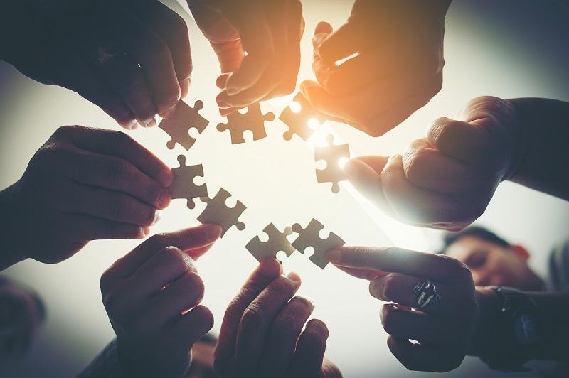 Mehrere Personen halten jeweils ein Puzzleteil in ihren Händen und führen sie zusammen