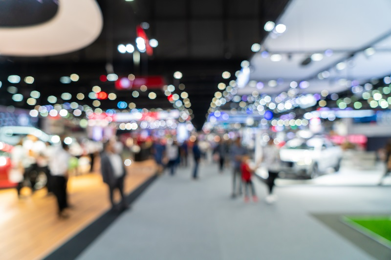 Personen gehen durch die Ausstellungsflächen einer Messe