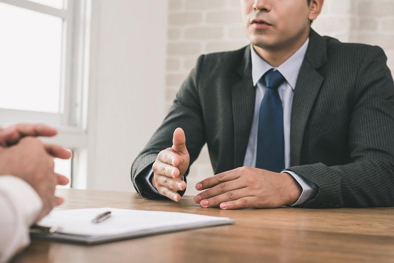 Zwei Männer sitzen sich gegenüber an einem Tisch und reden miteinander