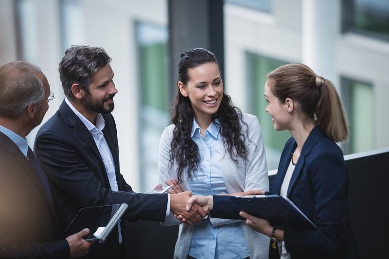 Mehrere Geschäftsleute unterhalten sich und reichen sich die Hand
