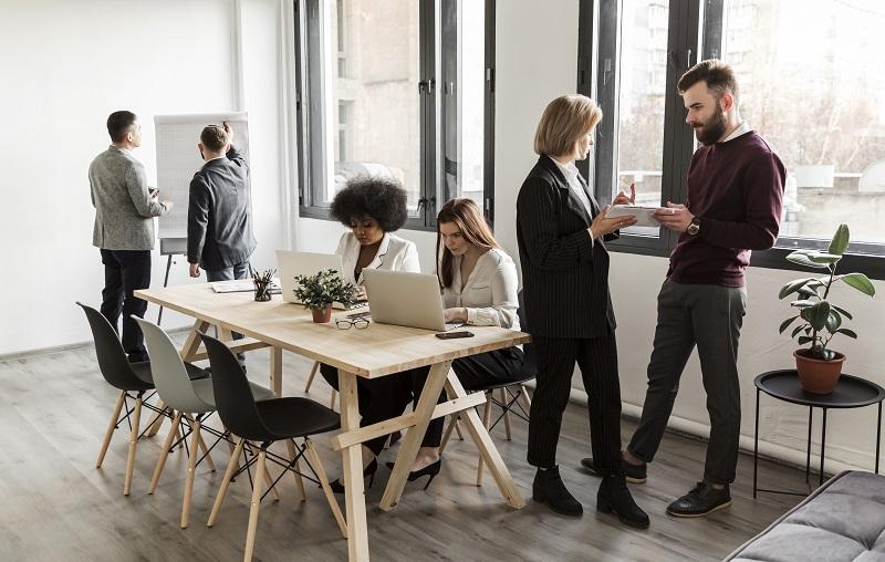 Mehrere Personen stehen und sitzen in einem Meeting-Raum zusammen und reden miteinander