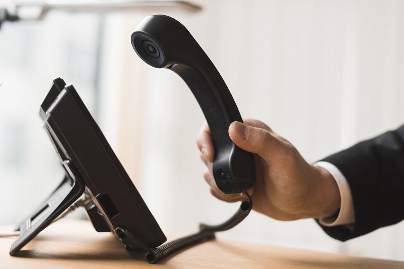 Ein Geschäftsmann nimmt einen Telefonhörer in die Hand